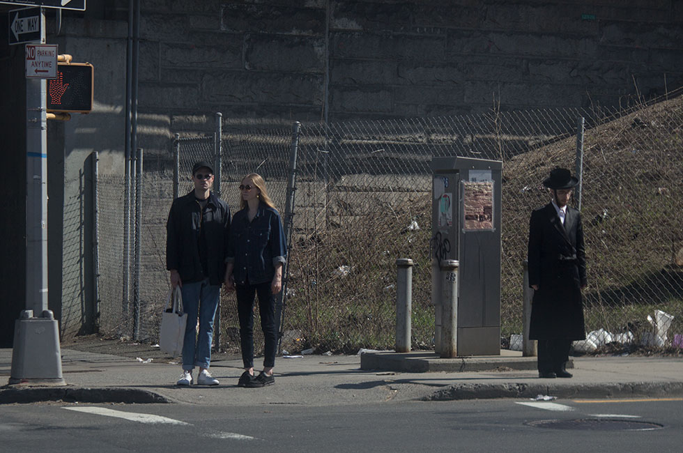 Hip couple waiting at crossing with hasidic man